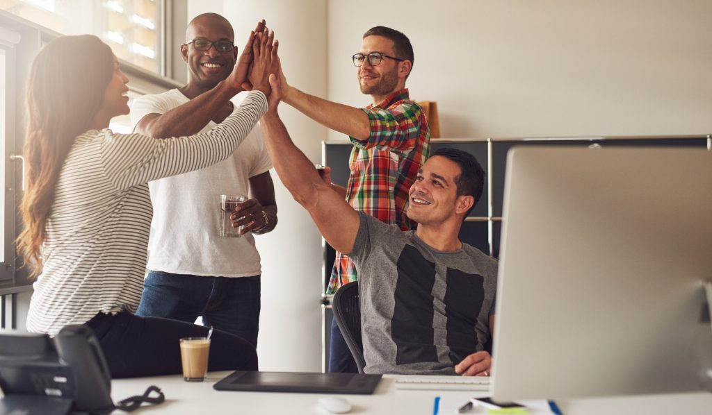 Diverse workers celebrating something in office
