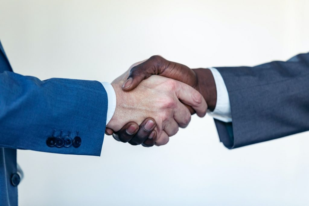 Close-up view of business partner handshaking process.