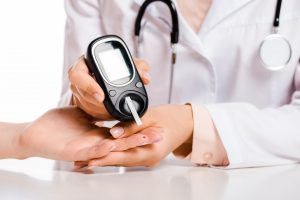 cropped image of doctor measuring patient level of glucose in blood with glucometer isolated on