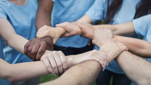 Hands of young people joined in circle
