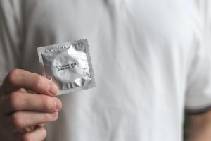Male hand holding condom.