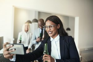 Smiling African American businesswoman having office drinks and taking selfies