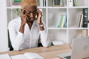 stressed african american businesswoman holding head