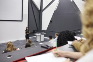 Woman lecturing students in a lecture theatre, mid row POV