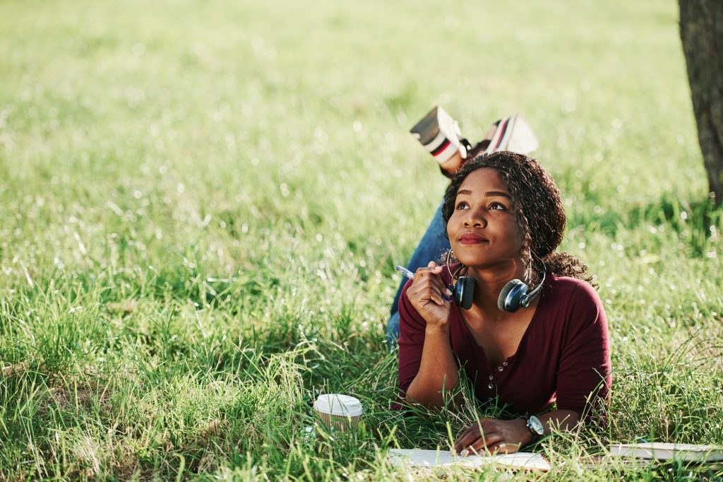 Writer thinks how to finish the chapter. Cheerful african american woman in the park at summertime