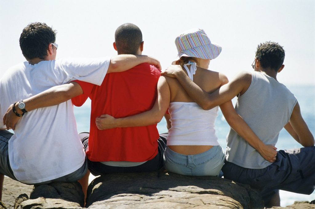 Back view of four friends, with arms around each other, sitting in a row.