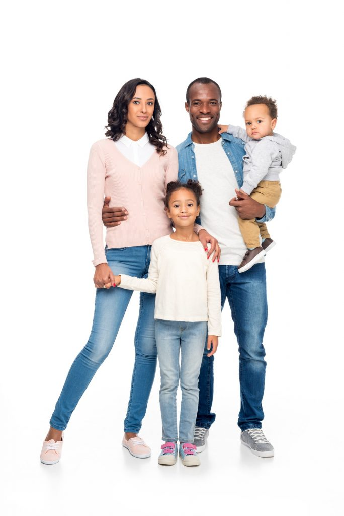 beautiful happy african american family with two children standing together and smiling at camera