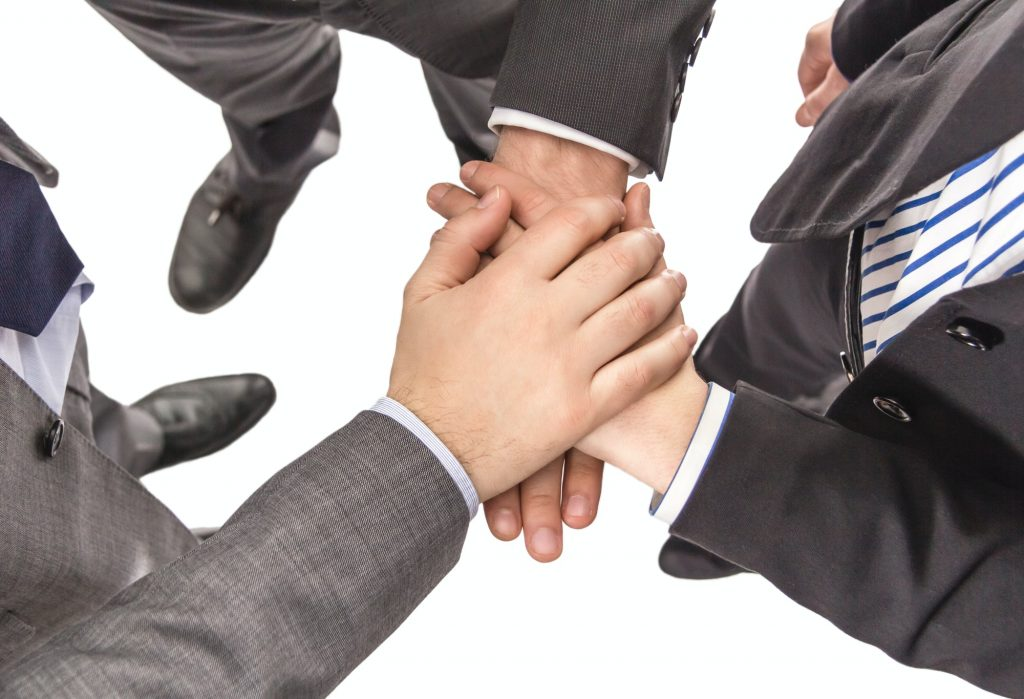Business partners with hands above showing power and unity