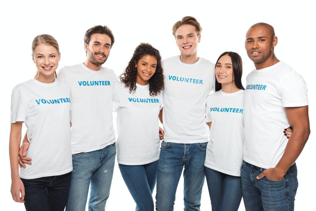multiethnic group of embracing volunteers looking at camera isolated on white