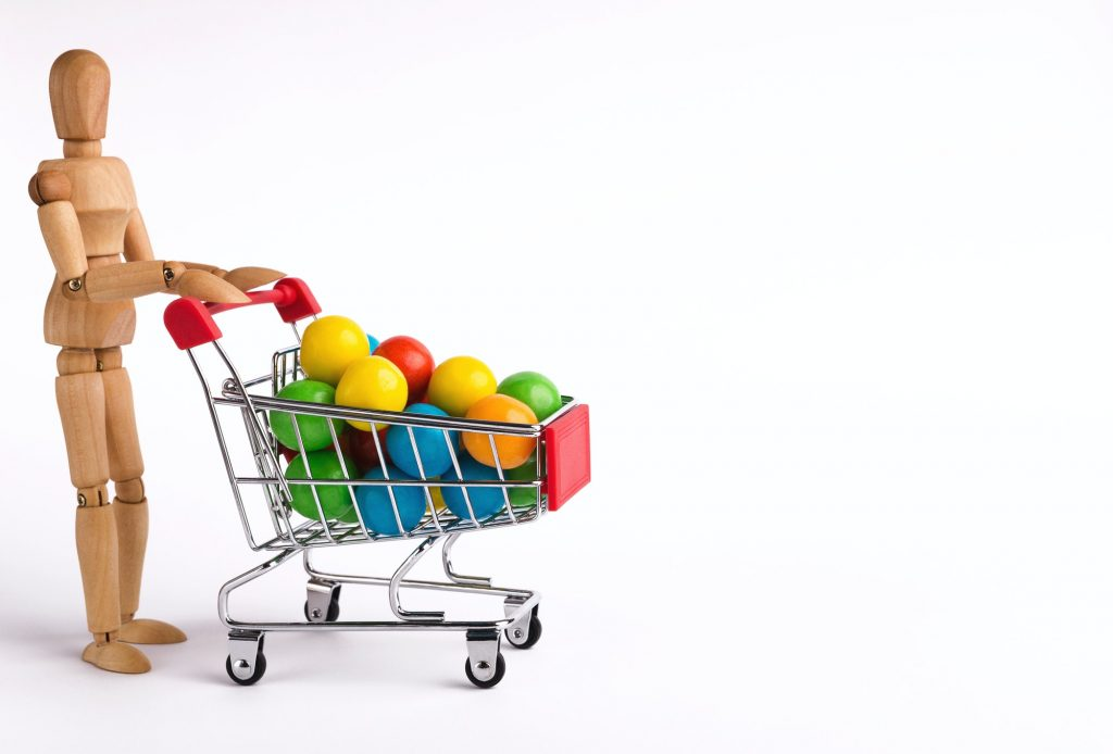 Wooden man with colorful candies in shopping trolley